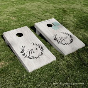 Cornhole boards with floral wreaths that say Mr and Mrs