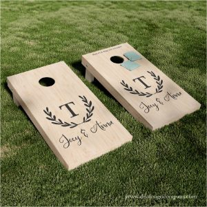 Cornhole board decals with a monogram inside a wreath and names below it.