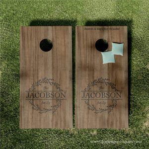 Cornhole boards with floral wreath and last name in the middle