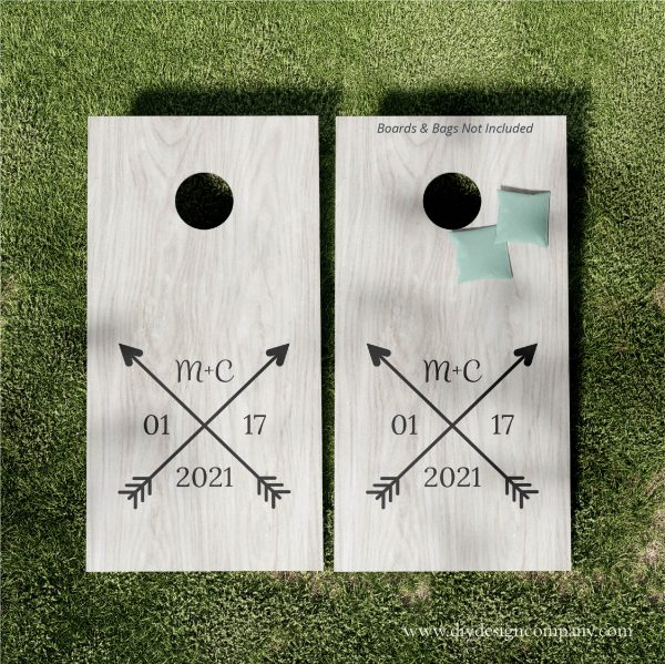 Cornhole boards with crossed arrows, initials and wedding date